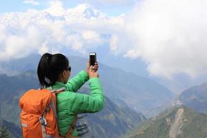 jonge Aziatische vrouw die backpacker foto met smartphone neemt