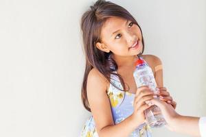 helpende hand die een fles water geeft aan arme kind foto