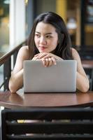 Aziatische vrouw die gelukkig een notitieboekje gebruikt