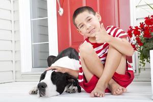 jonge jongen duimen opgevend, zittend door zijn hond foto