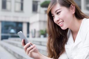 Aziatische mooie vrouwelijke student met behulp van mobiele telefoon op de campus foto