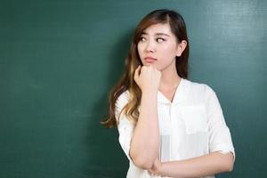 Aziatische mooie vrouw die zich voor bord met gebaar bevindt foto