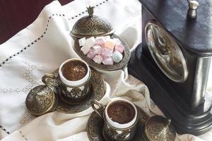 Turkse koffie met verrukking en traditionele serveerset, vintage klok foto