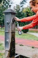 vrouw gieten van water in een sportfles foto