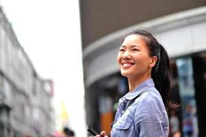 vrouw met behulp van haar mobiele telefoon in de straat foto