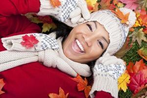 glimlachende vrouw die op de herfstbladeren legt foto