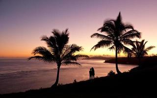paar kijken naar zonsopgang in Kauai foto