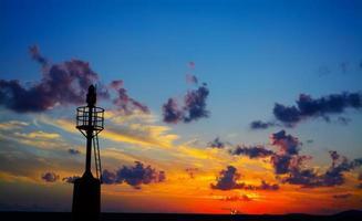 vuurtorensilhouet bij zonsondergang in alghero
