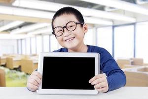 gelukkig schooljongen met lege tablet-scherm foto