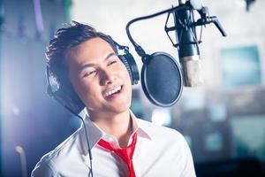 Aziatische mannelijke zanger produceren lied in opnamestudio foto