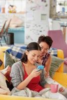 multi raciale vriendinnen vlechten haar lachend met behulp van mobiele telefoon foto