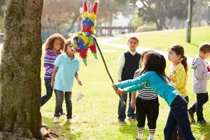kinderen raken pinata op verjaardagsfeestje foto