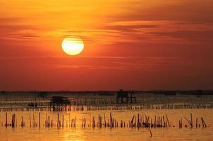 silhouet van Thais vissershuis bij zonsondergang foto