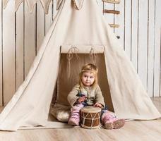 klein meisje met trommel in de buurt van wigwam foto