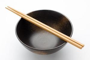 eetstokjes en zwarte kom foto