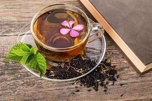 thee met roze bloem en muntblad, op hout