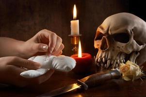 handen steken een speld in een voodoo-pop met een schedel en mes