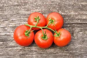 rijpe tomaat op houten achtergrond foto