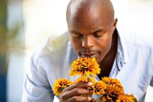 Afrikaanse man ruikende bloemen in een bloementuin foto