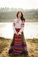 jonge vrouw in Slavische Wit-Russische nationale oorspronkelijke pak buitenshuis