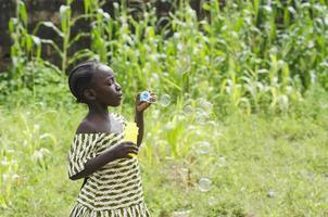 Afrikaanse meisje speelt met zeepbellen buiten in Bamako, Mali foto