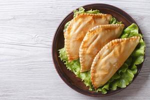gevulde empanadas op een bord. horizontale weergave van bovenaf foto