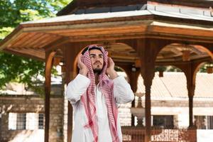 jonge moslim man bidden foto