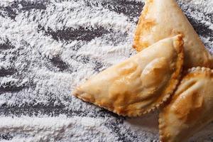 taarten empanadas close-up op een bebloemde tafel. horizontaal bovenaanzicht foto