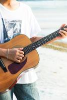 jonge man gitaarspelen op het strand