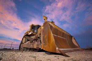 gele bulldozer werken bij zonsondergang foto