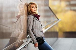 jonge mode blonde vrouw die zich aan de muur