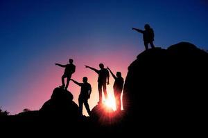 mensen bovenop rotsachtige bergen foto