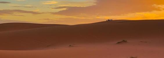 Sahara woestijn Marokko. mensen in de verte kijken naar zonsopgang. foto