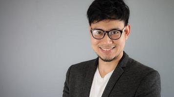 Aziatische zakenman in zwart pak met grijze achtergrond. foto