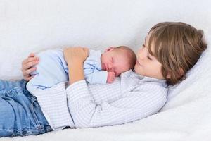 pasgeboren babyjongen slapen in de armen van zijn broer foto