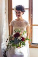 jonge en aantrekkelijke bruid zitten bij het raam foto