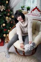 lachende brunette zittend in de fauteuil foto