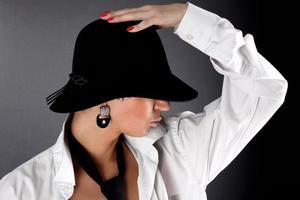 mode jonge vrouw in hoed verbergend oog
