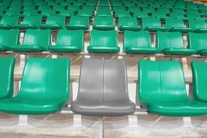 grijze stadionstoel tussen groene stoelen foto