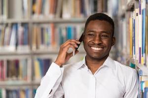 mannelijke student praten over de telefoon in de bibliotheek foto