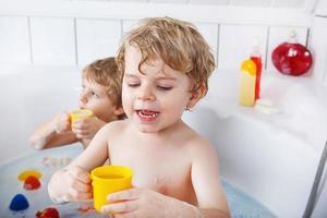 twee kleine tweelingjongens die een bad nemen foto