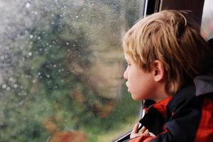 7 jaar oude jongenszitting in de trein foto