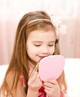 schattig klein meisje met lippenstift foto