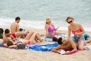 mensen zonnebaden op het strand foto
