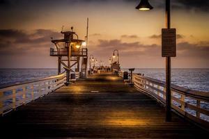 mensen lopen een pier bij zonsondergang foto