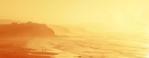 mensen in sopelana strand met nevel foto