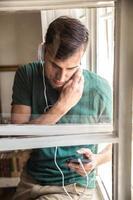 man die bij het raam staat en naar muziek luistert foto