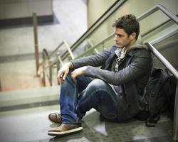knappe jonge man zittend op trappen foto