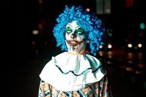 gekke boze clown in de stad op halloween die mensen bang maakt