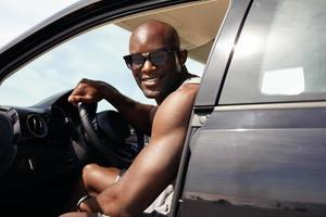 gelukkige jonge kerel in zijn auto foto